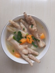 Chicken feet soup in a white bowl isolated on beige background. Indonesian chicken feet soup with carrot, cabbage, and celery also known as sop ceker. Chicken feet and vegetable soup in a white bowl
