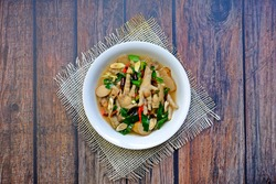 Chicken feet spicy and sour soup in white bowl on wooden table. Authentic Thai food.