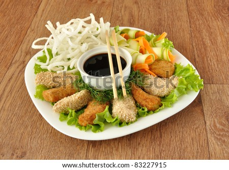 Chicken fillet in breadcrumbs and sesame with fried rice noodles with vegetables