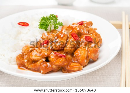 chicken fillet in tomato sauce with sesame seeds and rice close-up, horizontal