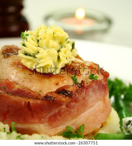 Chicken fillet mignon wrapped in bacon on parsley mashed potato with green beans.