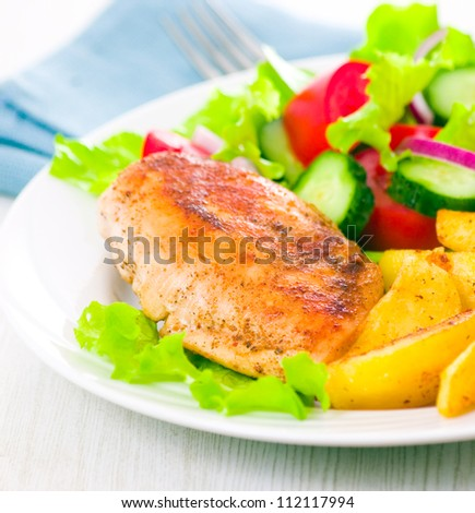 chicken fillet with fresh vegetable salad and potato