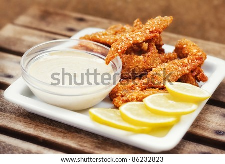 Chicken fingers served with tartar sauce and lemon slices  (shallow dof)