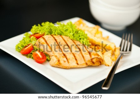Chicken, French fries and salad in a nice setting