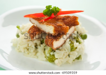 Chicken fried with eggs and bread crumbles and served with peas risotto