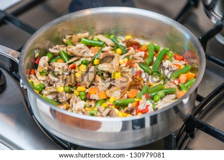 Chicken fried with vegetables on a sauce pan
