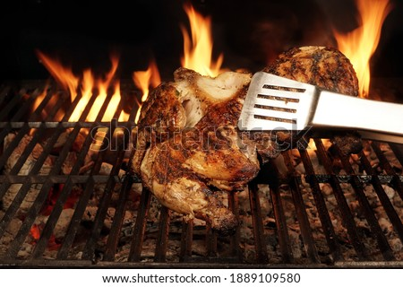 Chicken Grilled On Hot Barbecue Charcoal Flaming Grill. Juicy Whole Chicken Meat Roasted on BBQ Grill. Backyard Grill Party Dish From Poultry Isolated On Black Background, Closeup View.