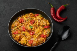 Chicken Handi in black bowl on dark slate table top. Murgh Chicken is indian cuisine curry masala dish. Asian food and meal.