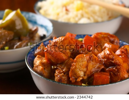 Chicken in yellow bean sauce, with diced carrots, cashew nuts, accompanied in the background (out of focus) by beef with peppers and rice