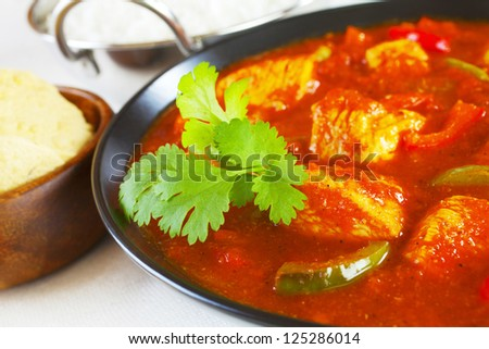 Chicken Jalfrezi with rice and poppadums. This curry was invented by Indian chefs in the time of the Raj, when left over roast chicken would have been combined with spices and vegetables.