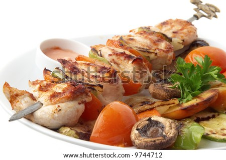 chicken kebab with grilled vegetables on white plate, selective focus