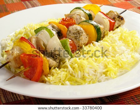 Chicken kebabs with bell peppers, onions, zucchini, and cherry tomatoes. Served with saffron flavored basmati rice. - stock photo