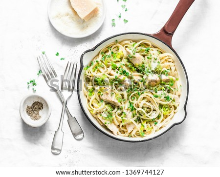 Photo of  Chicken, leek, linguine pasta carbonara in a frying pan on a light background, top view. Flat lay