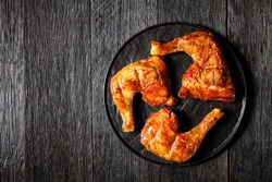 Chicken leg quarters, baked in the oven, skin-on, bone-in, served on a black plate, top view, close-up