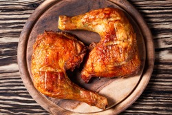 Chicken leg quarters, baked in the oven, skin-on, bone-in, served on a wooden background, top view, close-up