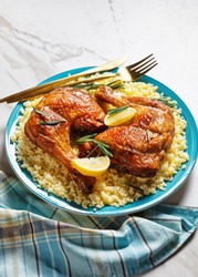 Chicken leg quarters served over the millet on a plate with golden cutlery, lemon wedges, and fresh rosemary sprigs on a white marble stone background, top view, close-up