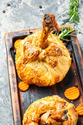 Chicken legs in pastry.Chicken leg in puff pastry on cutting board.Baked chicken drumsticks on cutting board