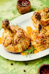 Chicken legs in pastry.Chicken leg in puff pastry on table.Baked chicken