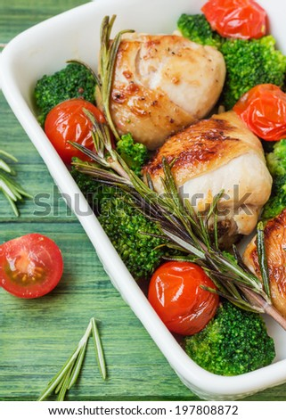 Chicken legs with cherry tomatoes, broccoli, rosemary in a white bowl on the background of the tree.