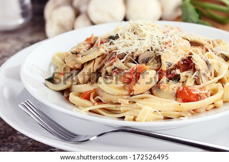 Chicken linguine with grilled chicken, tomatoes, mushrooms and freshly grated parmesan cheese. Fresh mushrooms and herbs in background.