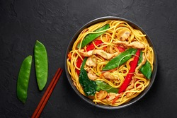 Chicken Lo Mein in black bowl at dark slate background. Lo Mein is Chinese cuisine dish with chicken meat, egg noodles, vegetables and sauces. Chinese Food. Stir Fried Noodles. Copy space. Top view