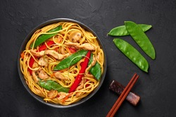 Chicken Lo Mein in black bowl at dark slate background. Lo Mein is Chinese cuisine dish with chicken meat, egg noodles, vegetables and sauces. Chinese Food. Stir Fried Noodles. Top view