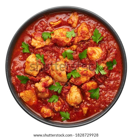 Chicken Madras Curry in black bowl isolated on white. Indian cuisine dish with with chicken meat and spicy masala gravy. Asian food and meal.