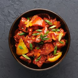 Chicken Manchurian in bowl at black concrete background. Chicken Manchurian is Indian Chinese cuisine dish with Chicken breasts, bell pepper, tomatoes, soy sauce.