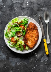 Chicken milanese and fresh romaine salad, cherry tomatoes, radishes, cucumbers salad - delicious lunch on a dark background, top view