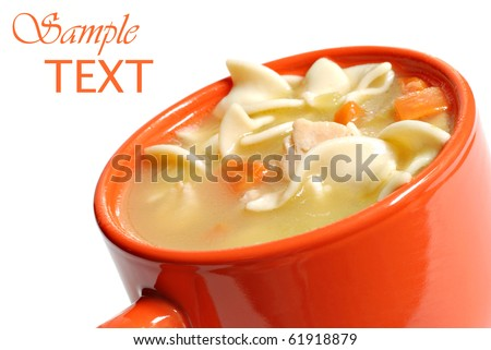 Chicken noodle soup in bright orange mug on white background with copy space.  Macro with shallow dof.