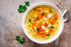 Chicken noodle soup with parsley and vegetables in a white plate, gray background.