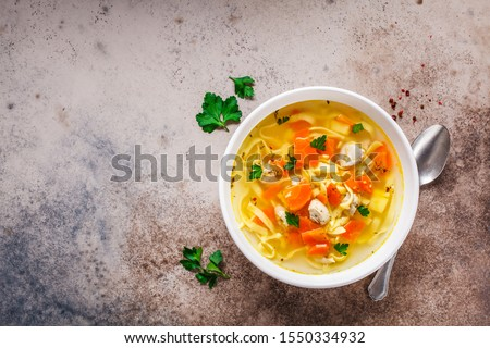 Chicken noodle soup with parsley and vegetables in a white plate, gray background. Сток-фото ©