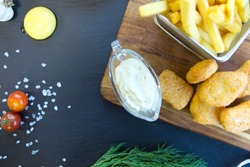 Chicken Nuggets and Chips with sause on wooden cutting board.