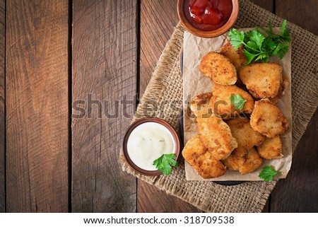 Chicken nuggets and sauce on a wooden background. Top view Сток-фото ©