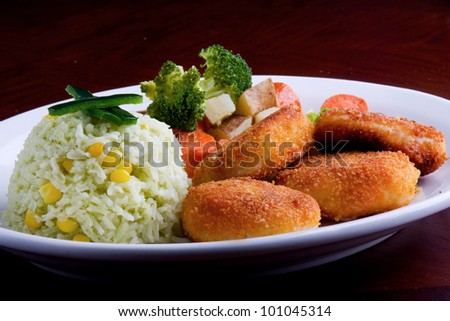 chicken nuggets ? chicken nugget plate served with vegetables and a side of rice.