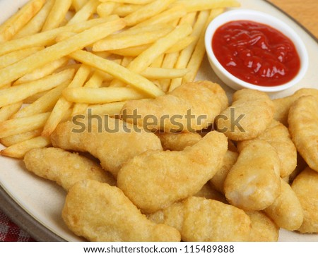 Chicken nuggets with fries and tomato ketchup.