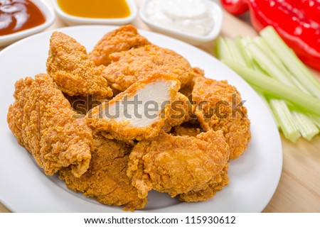 Chicken nuggets with three dipping sauces.