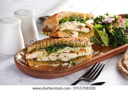 Chicken Panini has Chicken - pesto - mozzarella - rocket - olive panini bread in brown wooden plate, on white background  Stok fotoğraf ©