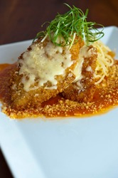 Chicken Parmesan. Chicken breast breaded, fried topped with tomato sauce, mozzarella cheese, Italian parsley and served with angel hair pasta dressed in olive oil. Classic Italian entree favorite.
