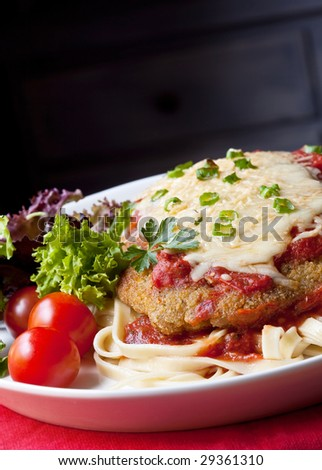Chicken parmesan or parmigiana, with melting mozzarella and parmesan cheeses, over fettucine ribbon pasta. - stock photo