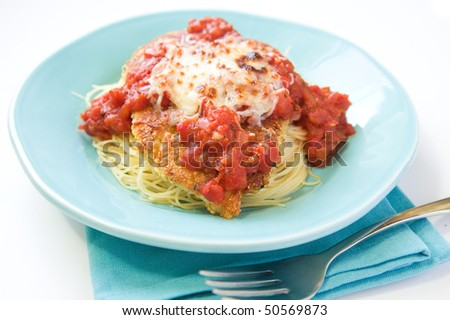 Chicken parmesan with a thick sauce served over pasta