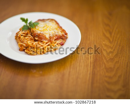 Chicken parmigiana on a white plate and wooden table - stock photo