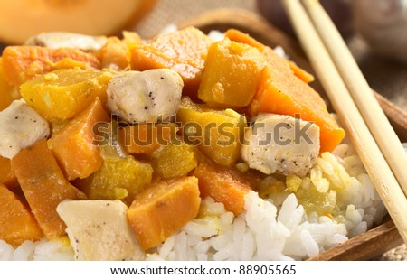 Chicken, pumpkin and sweet potato curry served on rice in wooden plate with chopsticks (Selective Focus, Focus on the meat piece on the right and on the top)