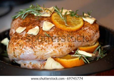 chicken ready for roasting with rosemary, oranges and honey on top