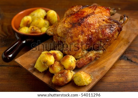 chicken roasted with potatoes on wood background