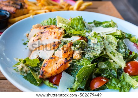 Chicken Salad. Chicken Caesar Salad. Caesar Salad with grilled chicken on plate. Grilled chicken breasts and fresh salad in plate #502679449