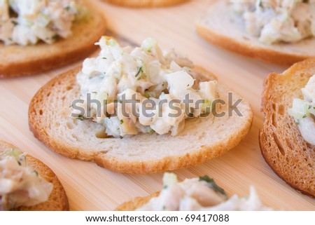 Chicken salad with celery, onion, and parsley on melba toast.