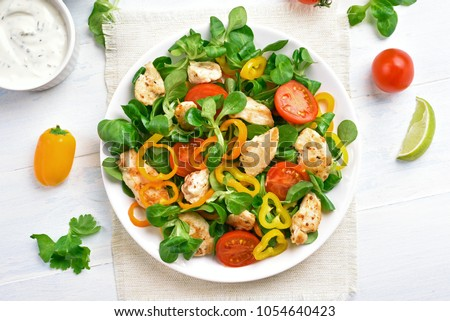 Chicken salad with vegetables on white wooden table. Top view, flat lay