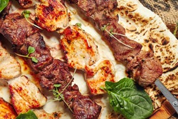 Chicken, Salmon and Meat Shish Kebabs on Parchment with Sauces Top View