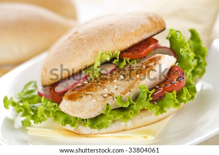 Chicken sandwich with salad and tomato close up